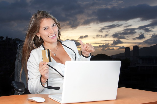 attractive woman holding credit card out in front of notebook computer